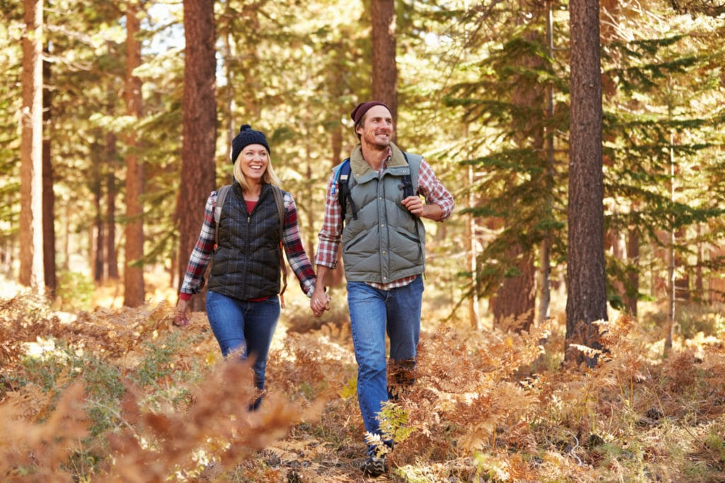 Young couple hiking in the woods in the fall and exploring scenic places in CT